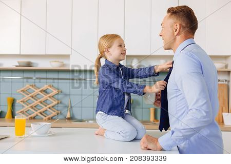 Formal style. Happy nice positive girl smiling and looking at her father while helping him to get dressed