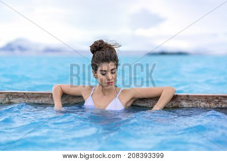 Sensual girl with closed eyes in a white swimsuit leans on a wooden crossbeam in the geothermal pool on the background of snow mountains and cloudy sky outdoors in Iceland. Horizontal.