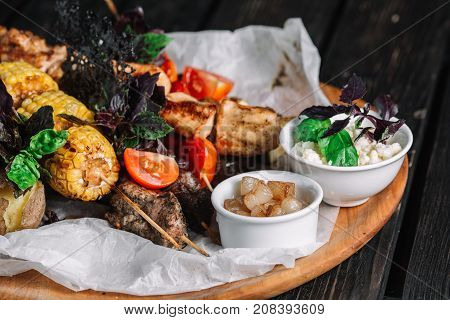 Assorted delicious grilled meat with vegetable served with cracklings and brynza on a wooden board on dark wood background