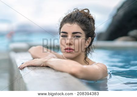 Sexy girl in a white swimsuit leans on the edge of the geothermal pool outdoors in Iceland. She looks into the camera with parted lips. Closeup. Horizontal.
