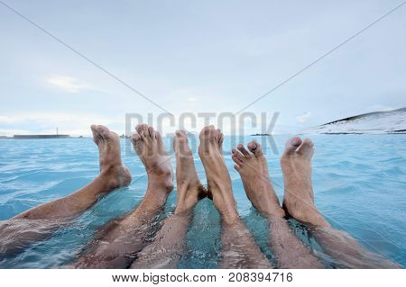 Three pairs of legs in the geothermal pool on the background of snow mountains and cloudy sky outdoors in Iceland. Closeup. Horizontal.