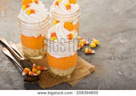 Halloween dessert in a jar layered candy corn parfait with cream cheese
