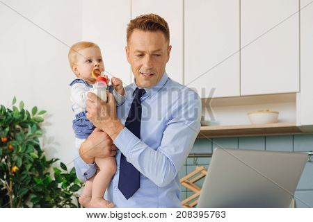 Paternity leave. Pleasant nice handsome father holding his baby daughter and feeding her with milk while looking at the laptop screen