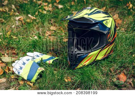 Environmental Reservation Motorcycle Biker riding gloves and helmet on fallen leaves over grass background. Automne.