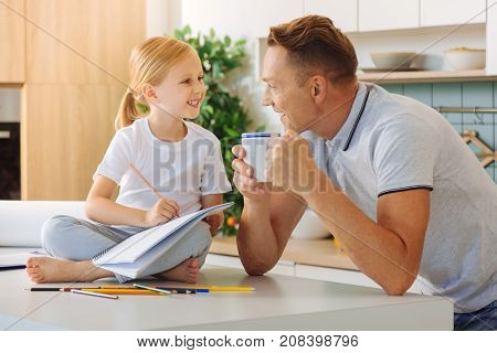 Interaction with daughter. Nice pleasant delighted man holding a cup of tea and smiling while talking to his daughter