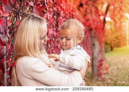 Beautiful Young Mom And Young Son Walk. Mom And Young Son Walk In Autumn Park. Red Autumn Leaves. Wa