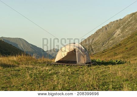 lightweight hiking dome tent on wooden floor in a tourist camp in the mountains