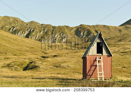a small wooden board house without windows and doors with a gable roof on a mountain plateau with a ladder leading to an open attic