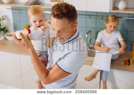 One parent family. Serious nice smart man holding a bottle with milk and feeding his child while standing in the kitchen
