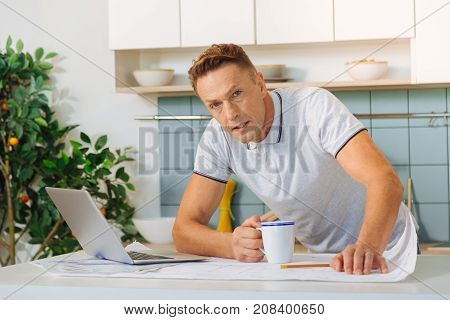 Tired from work. Serious unhappy adult man holding a cup of tea and feeling tired while working on a project