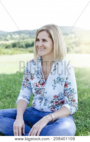 Happy Satisfied Woman Sitting In The Meadow