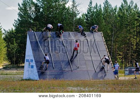 Tyumen, Russia - June 11, 2016: Race of Heroes project on the ground of the highest military and engineering school. High wall stage. Sportsman storms wall