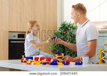 Thank you. Happy cheerful nice girl smiling and looking at her father while taking a constructor set piece