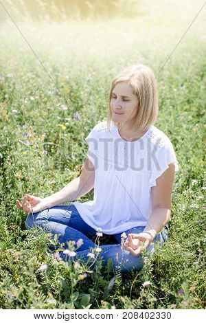 Happy Woman Is Doing Yoga In The Meadow