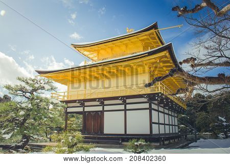 Beautiful winter seasonal of Golden Pavilion of Kinkakuji Temple with white snow falling and blue sky background at Kyoto, Japan.