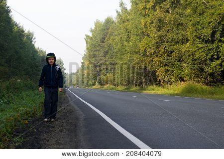 A boy in a dark hooded sweatshirt walks along the roadside in a beautiful forest