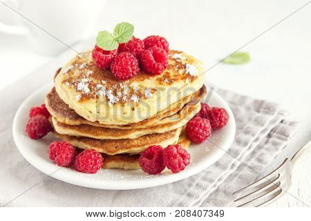Stack of fresh pancakes with berries (raspberries) on white plate copy space - healthy homemade vegan vegetarian diet fresh organic breakfast food