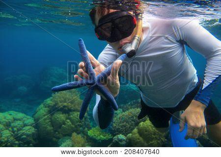 Man snorkeling in blue water with star fish. Snorkeling in coral reef. Snorkel holds blue starfish. Marine animal in wild nature. Tropical seashore aquatic life. Man in snorkeling mask undersea photo