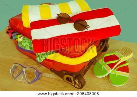 Suitcase with different things prepared for travel. Travel and vacations concept. Suitcase with things for spending summer vacation - Retro color