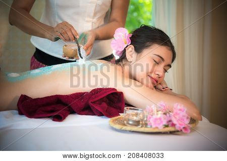 Masseur doing massage spa with treatment salt and sugar on Asian woman body in the Thai spa lifestyle so relax and luxury. Healthy Concept