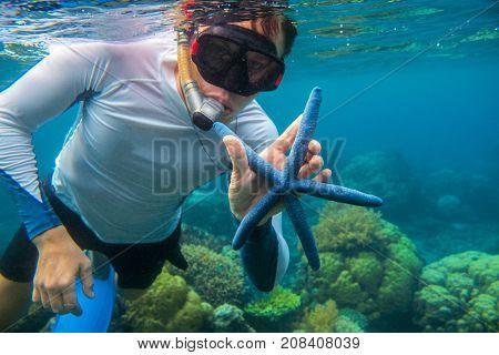Man snorkeling in blue water with starfish. Snorkeling in coral reef. Snorkel holds blue starfish. Marine animal in wild nature. Tropical seashore aquatic life. Man in snorkeling mask underwater photo