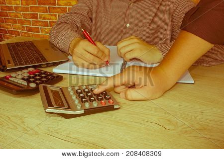 Two man accountants counting on calculator income for tax form completion hands closeup. Internal Revenue Service inspector checking financial document. Planning budget audit concept - Retro color