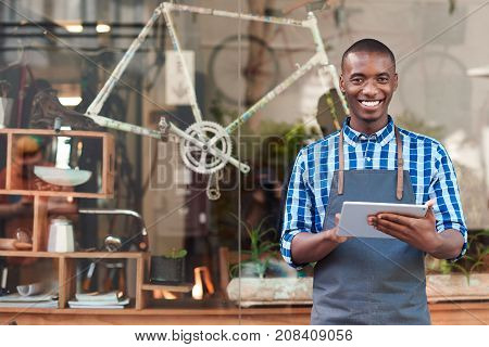 Portrait of a smiling young African entrepreneur wearing an apron and standing in front of his trendy cafe working online with a digital tablet