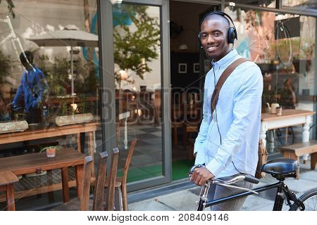 Stylishly dressed young African man smiling and listening to music on headphones while standing with his bicycle on a city street