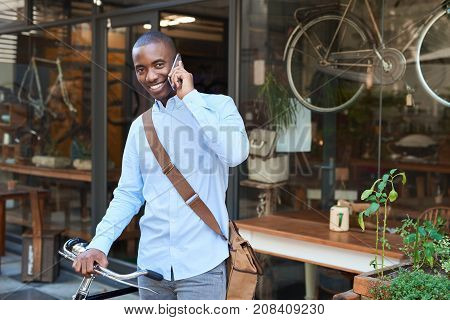 Portrait of a stylishly dressed young African man talking on his cellphone while walking with his bicycle down a city street