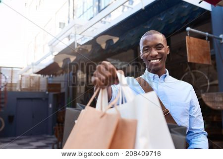 Portrait of a stylishly dressed young African man smiling and holding up shopping bags while out shopping in the city