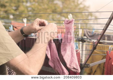 Domestic chore, hanging washing out to dry outdoors.