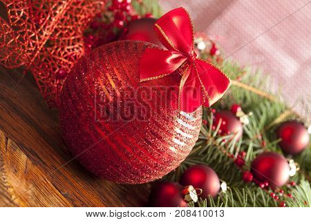Christmas bauble with red bow on wooden table