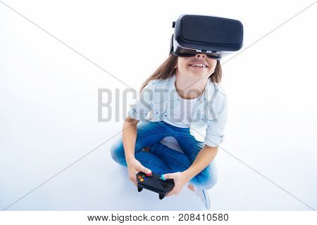 Video games. Delighted positive cute girl holding a game console and having fun while playing a game in virtual reality