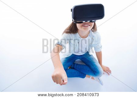 3d reality. Positive cheerful young girl sitting on the floor and smiling while being in 3d reality