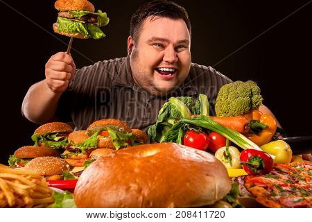 Diet fat man who makes choice between healthy and unhealthy food. Overweight male with hamburgers, french fries and vegetables trays trying to lose weight on black background. Semi-finished products.