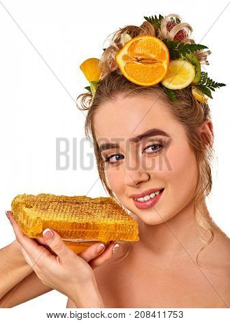 Honey facial mask with fresh fruits for hair and skin on blond woman head. Girl with beautiful face hold honeycombs for homemade organic skin and hair therapy. Acceleration of hair and eyebrows growth