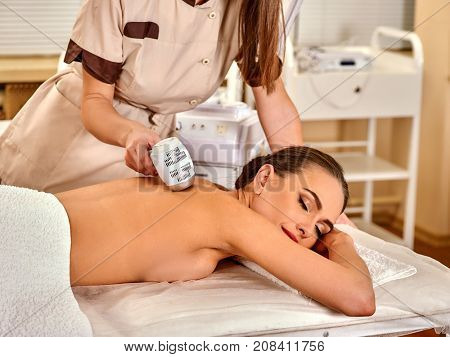 Ultrasonic body treatment on ultrasound skin care machine. Woman on lift massage at spa salon. Electronic stimulation muscles. Professional microcurrent therapy. The best spa salon.