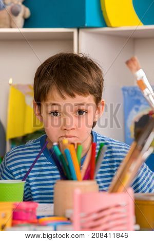 Child boy does study homework tips. Difficulties with homework for school children. Small students painting in art school class.