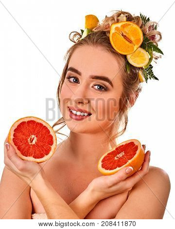 Hair mask from fresh fruits on woman head. Girl with beautiful face holds halves of grapefruit for homemade organic skin and hair therapy. Acceleration of hair growth.