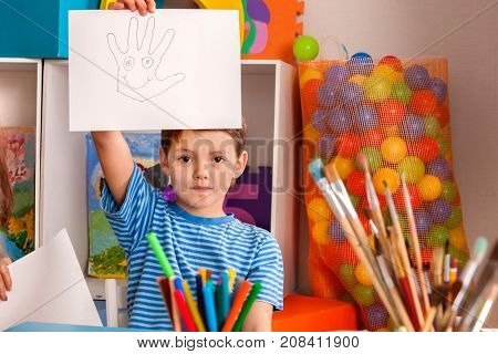 Child in world peace day . Boy picture hand with smile concept. Small students painting picture on topic be positivein art school class.