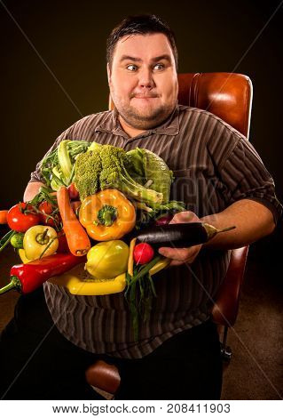 Diet fat man eating healthy food with vegetables cauliflower and sweet pepper with radish, tomatoes for overweight male. Male trying to lose weight first time. Hungry person ready to eat everything.