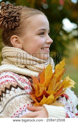 portrait of pretty little girl with apple and maple leaves  in autumnal park
