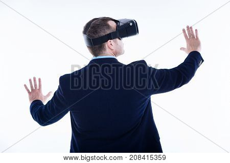 Another dimension. Nice handsome adult man turning his back to you and moving his arms while being in virtual reality