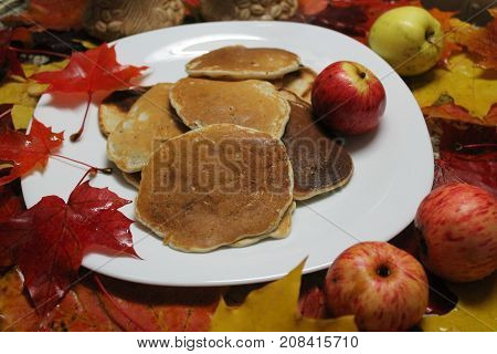 appetizing golden pancakes on the plate with juicy apples decorated bright foliage
