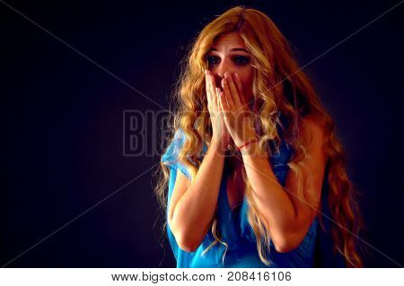 Shocked woman screaming with joyful. Surprised excited happy girl in light dress shouting with joy or fright and cuddle her hands to her cheeks She is frightened by unpleasant news Halloween discounts