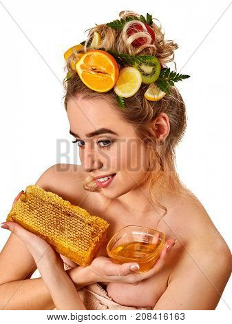 Honey facial mask with fresh fruits for hair and skin on blond woman head. Girl with beautiful face hold honeycombs for homemade organic skin and hair therapy. Acceleration of hair growth.