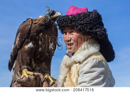 BAYAN-ULGII, MONGOLIA - SEP 30, 2017: Kazakh Eagle Hunter traditional clothing, while hunting to the hare holding a golden eagle on his arm in desert mountain of Western Mongolia.