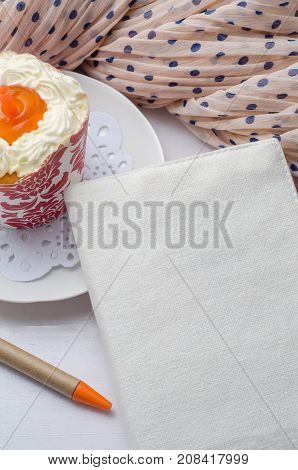 Blank notebook with pen and cupcake on wooden table.