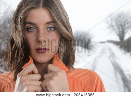 Digital composite of Woman holding her jumper tight keeping warm in snow countryside