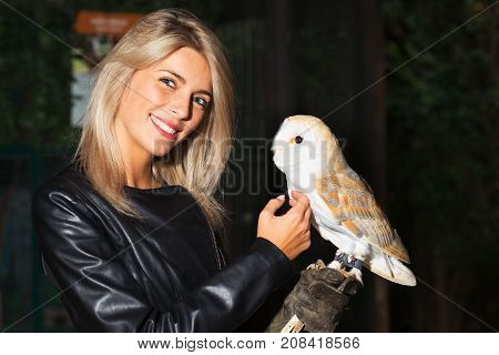 Beautiful Blond Girl Caresses On Her Chest A Barn Owls